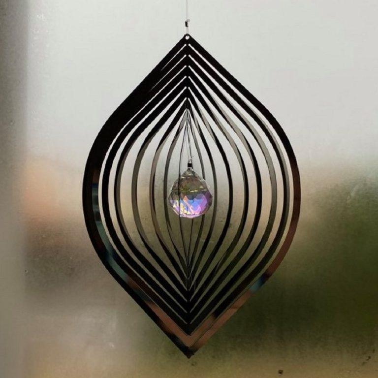 Spinner à vent en métal avec effet d'optique 3D. La suspension décorative est en forme de goutte avec un réflecteur de lumière en son milieu en forme de Cristal